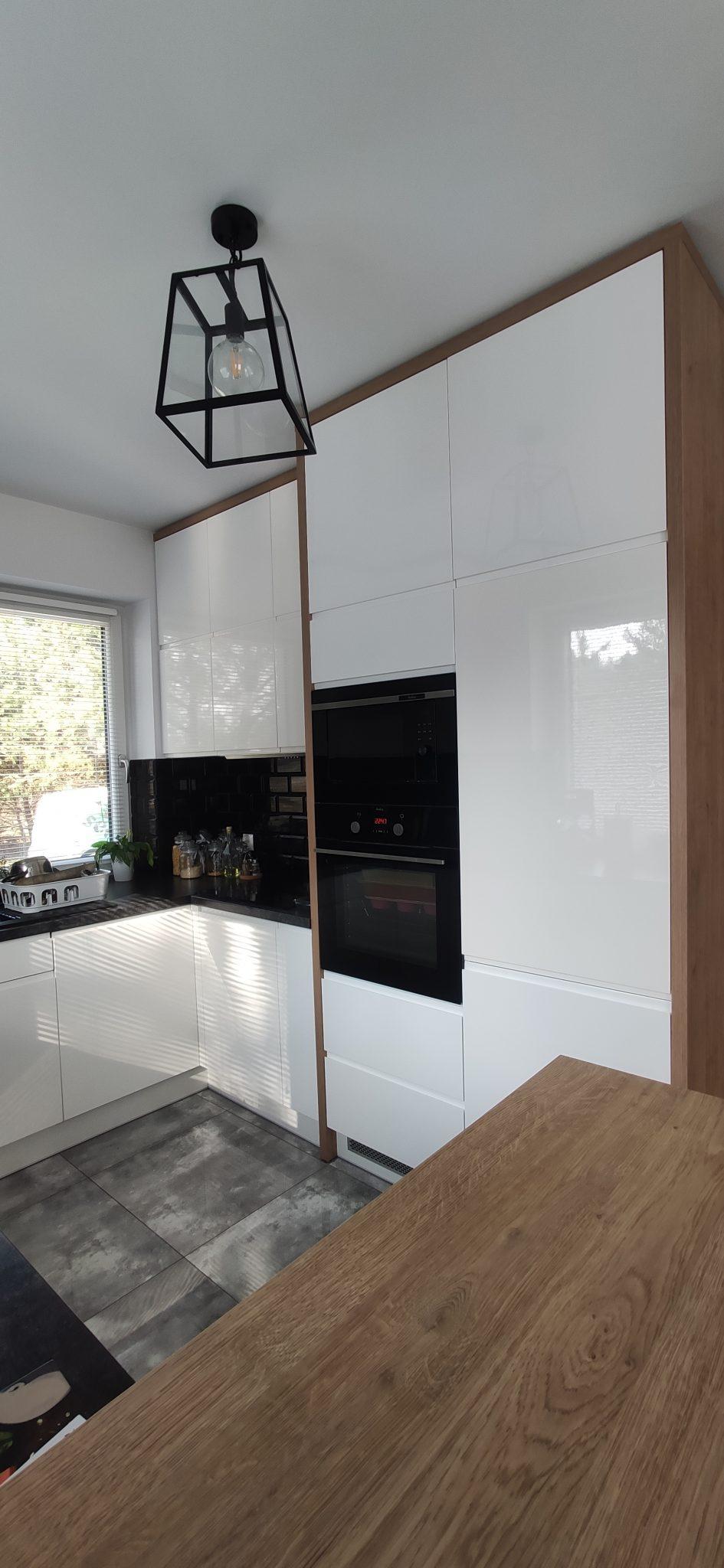 Sekwoja Dębica - Nowoczesna kuchnia dominująca bielą z dodatkami drewna i kontrastującej czerni